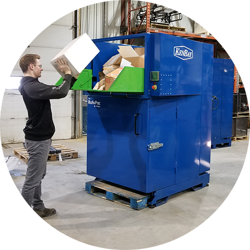 Man throwing boxes into an industrial trash compactor
